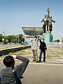Tourists taking picture in front of Worker and Kolkhoz Woman monument, rebuilt Russian Pavilion from Expo 67 in background, All-Russian Exhibition Centre, Moscow, Russia, before 2003