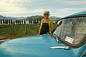 Lois Mills and Morris Minor car at Rippon Vineyards, Otago, South Island