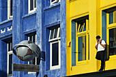 Telephoning outside coloured facade, Man with mobile phone outside building first floor, telefonieren mit Handy am Bunten Gebaudefassade, lifestyle