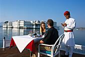 Couple having breakfast on the terrace of Lake Palace Hotel, Lake Pichola, Udaipur, Rajasthan, India, Asia