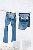 Jeans trousers and jeans skirt drying on clothesline, Bavaria, Germany