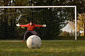 Young goalkeeper awaiting penalty, arms outstretched