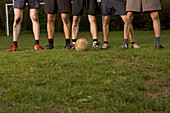 Legs of five young male soccer players, standing in a row