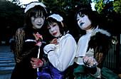 Three girls dressed-up in costumes posing for Photo, Harajuku, Jingumae quarter, Shibuya ward, Tokyo, Japan