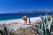 Mother walking with daughter 4-6, on beach near Gythio, Lakonia, Peloponnese, Greece