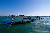Tourists enjoy a romantic ride in gondolas around Venice. Italy