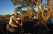 Swagman camps by a billabong with dog, Queensland, Australia