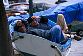Siesta, old men lying in a boat, Vernazza, Cinque Terre, Liguria, Italy, Europe
