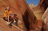 Woman having a rest during a hiking tour, Coyote Butes, Arizona, Utah, USA