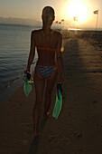 Woman walking along the beach at sunset, after freediving, Soma Bay, Hurghada, Egypt