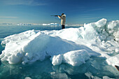 A hunter with a rifle standing on an ice floe, Ilulissat, Greenland
