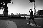 Woman practising Yoga in Battery Park, Manhattan, New York City, USA
