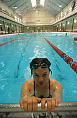 One young woman with swimming goggles in the water, City Baths, Swanston Street, Melbourne, Victoria, Australia