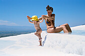 Woman with daughter splashing in limestone terraces, Pamukkale, Turkey