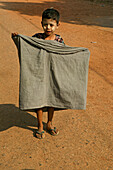 Child wrapping his longyi, Burma, Kind faltet sein Longyi, traditionelle Kleidung, traditional dress