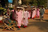 Nuns walk in a line to collect alms, Bago, Nonnen in rosa Roben, gehen in Reihe, Almosen sammeln, bekommen ungekochten Reis, Moenche, gekochten Reis