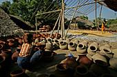 pottery workshop, woman kneeling, Myanmar