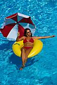 Frau im Wasser, mit Sonnenschirm und Reifen