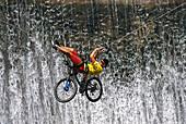 Mountainbiker an einem Seil vor Wasserfall