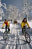 Zwei Frauen auf Fahrrädern auf verschneiter Strasse, Ramsau, Steiermark, Österreich, Europa