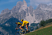 Bikers driving down an alpine pasture