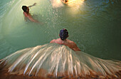 people in hotel thermal pool, Bagno Vignoni, Tuscany, Italy