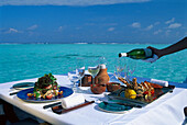 A table is laid on the waterfront in the sunlight, Four Seasons Resort, Kuda Hurra, Maledives, Indian Ocean