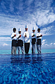 Cooks and waiters at the pool under clouded sky, Four Seasons Resort, Kuda Hurra, Maledives, Indian Ocean