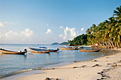 Fishing boats are moored in the shallow water off the beach, Taling Ngam, Koh Samui, Thailand