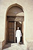 Ein Mensch geht durch eine Tür in das Fort, Nizwa, Oman