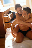 Couple on bed, woman embracing man form behind