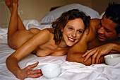 Naked couple lying on bed while drinking coffee