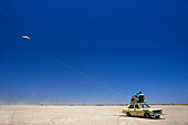 Two People on a car in the desert, hang-gliding in Namibia, Africa