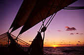 Romantic sunset on the horizon with bowsprit and net in the foreground, Traditional sailing Ship, Ocean, South Pacific