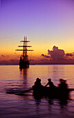 Boat rowing back towards the sailing ship at sunset, Traditional Sailing Ship, Cooks Bay, Moorea, French Polynesia, South Pacific, PR