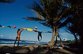Mann am Strand, Palmenstrand, Waescheleine, nackt Surfer