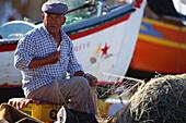 Fisherman repairing a fishing net at harbour, Algarve, Portugal, Europe