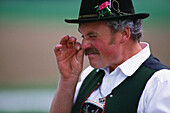 Man in traditional clothes taking snuff, Chiemsee Lake, Upper Bavaria, Germany