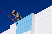 Local man painting his house blue, Thira, Santorini Cyclades, Greece