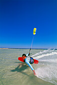 Young man kiteboarding, skimming hand across water