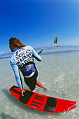 Young man with kiteboarding gear, ready for start