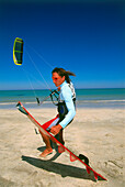 Young man on beach with kiteboarding gear, ready for start