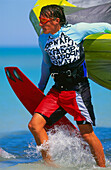 Man kiteboarding, holding kite and board