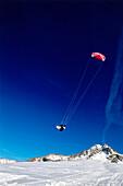 Man kiteboarding in snow, Jump, Lermoos, Lechtaler Alpen, Tyrol, Austria