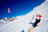 Young woman kiteboarding in snow, Lermoos, Lechtaler Alpen, Tyrol, Austria