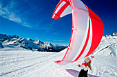 Young woman preparing kite for kiteboarding in snow, Lermoos, Lechtaler Alpen, Tyrol, Austria