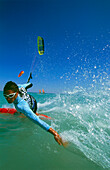 Man kiteboarding, holding hand into water