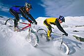 Young couple riding mountain bikes across snow, Serfaus, Tyrol, Austria