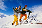 Young couple on slope with skifox and snowscoot, Serfaus, Tyrol, Austria