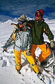 Young couple embracing on slope, holding skifox and snowscoot, Serfaus, Tyrol, Austria